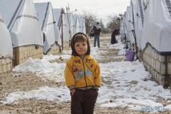 zaatari boy in yellow jacket snow